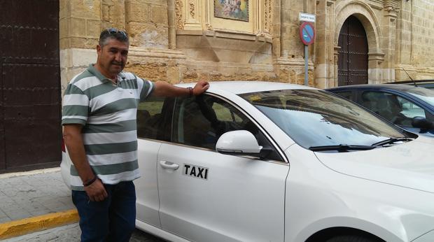 Antonio Cárdenas junto a su taxi en la plaza mayor de Osuna