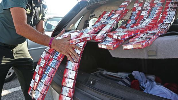 Un agente descarga decenas de cajetillas ilegales que estaban escondidas en el techo de un coche.