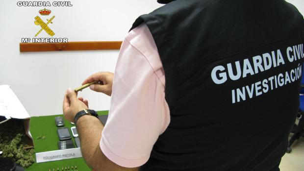 Un agente de la Guardia Civil, junto a la droga intervenida