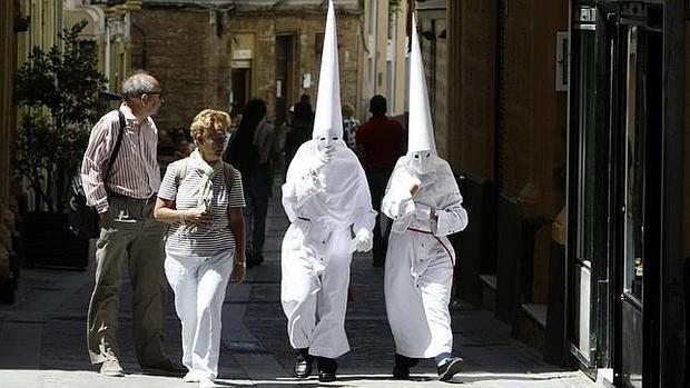 Turistas observan a dos penitentes en Cádiz