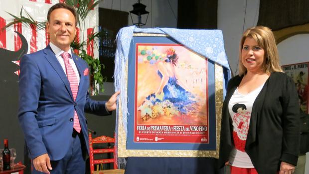 David de la Encina y Mamen Sánchez posan junto al cartel anunciador de la Feria de El Puerto de Santa María.