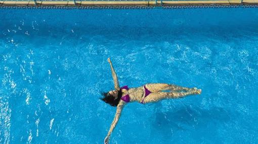 Una mujer se refresca en la piscina