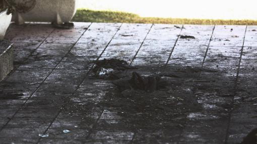Restos de la mesa quemada en el suelo del porche de la casa.