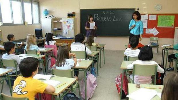 Alumnos asisten a una clase en un aula.