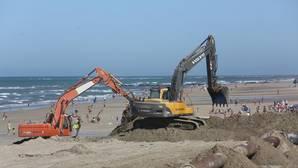 Los bañistas se topan con grandes excavadoras en la arena.