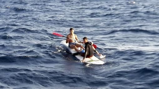 Dos chicos marroquíes intentan llegar en tabla de surf.