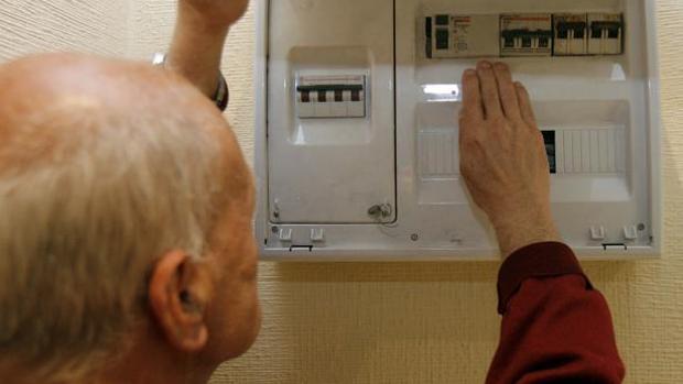 Un hombre observa el contador de luz de su casa.
