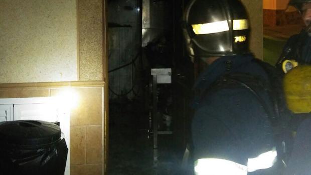 Bomberos durante la intervención del incendio en el bar
