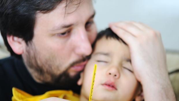 Un padre cuida a su hijo, enfermo de gripe.