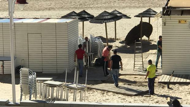 Los operarios desmontan las terrazas de uno de los chiringuitos de la playa Victoria
