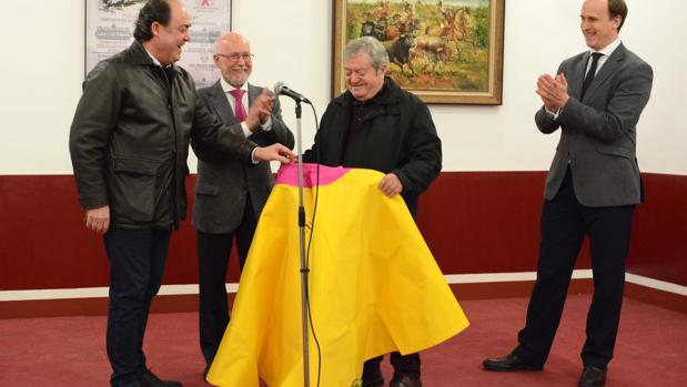 El pintor José López Canito recibe un capote firmado por el diestro Curro Romero