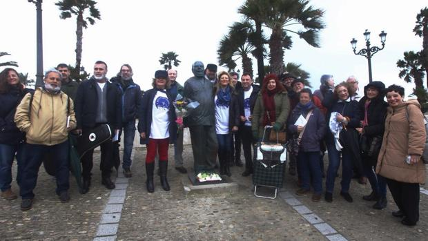 Algunos asistentes a la ruta junto al monumento en La Caleta