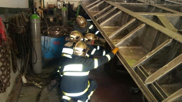 Los bomberos trabajan para retirar la plancha que ha aplastado a los dos trabajadores fallecidos.