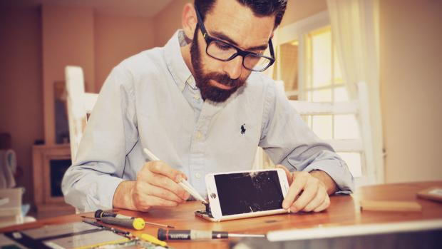 Julio González repara un dispositivo en un taller de trabajo. :: L.V.