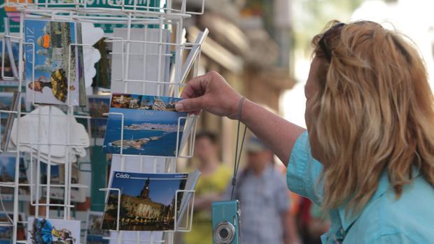 Una turista compra postales