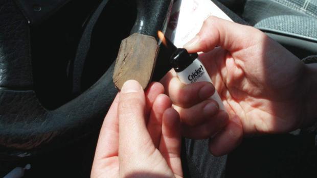 Un joven quema resina de hachís para liarse un porro