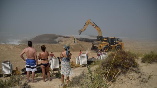 Los veraneantes observan los trabajos en la playa.