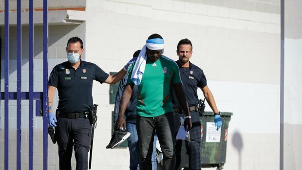 Agentes de la Policía Nacional trasladan a uno de los inmigrantes que han sido acogidos a su llegada en el pabellón de Algeciras