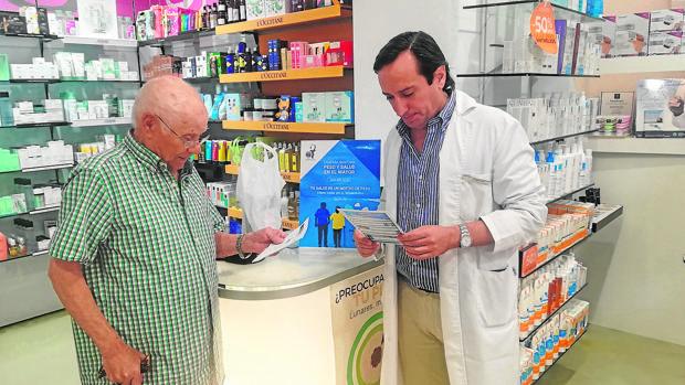 El impulsor de esta idea, Felipe Mozo, atendiendo a una persona mayor en la farmacia San Francisco de Cádiz