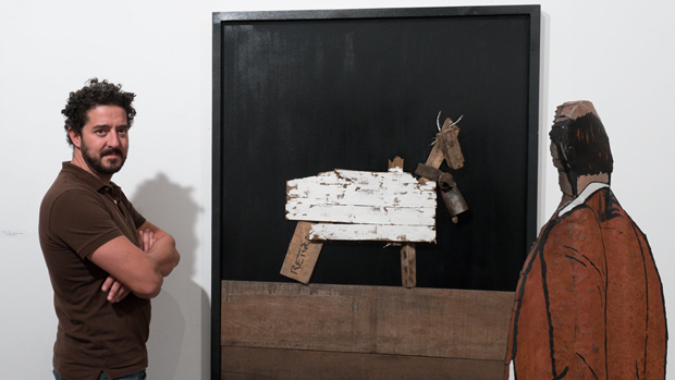 El artista gallego, Kike Ortega, posa junto a uno de sus trabajos