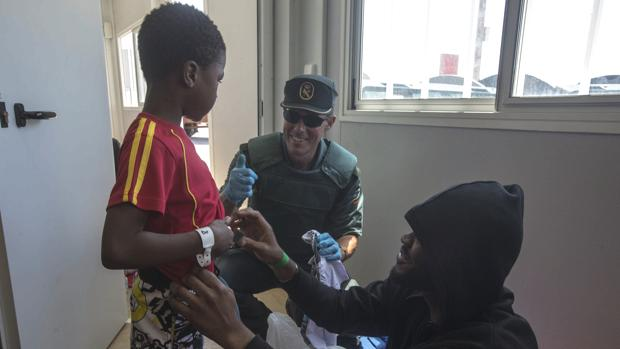 Un agente le regala al pequeño Mohamed, de seis años, algo de ropa.