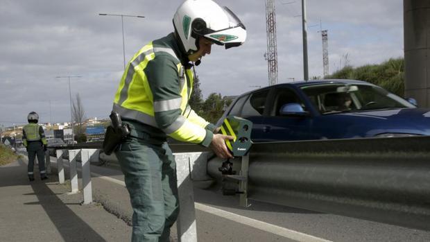 Un agente colocando el dispositivo en un quitamiedos de la carretera