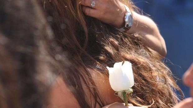 Una asistente al entierro de Sara Ojeda, fallecida en la deflagración del transformador situado en el '100% Fun', porta una rosa.