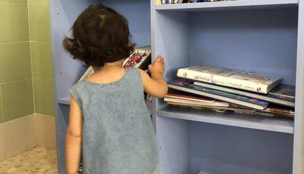 Una pequeña se interesa por los libros del punto de lectura