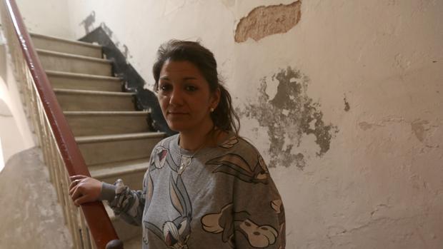 Vanesa, en la escalera de su vivienda con múltiples humedades en sus paredes.