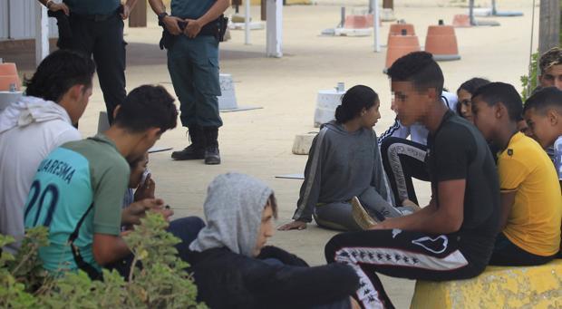 Dos agentes de la Guardia Civil vigilan a un grupo de menores llegados ayer en patera a la playa de Bolonia.