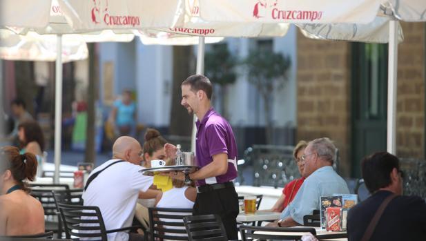 Un camarero presta sus servicios en una terraza de un bar de Cádiz