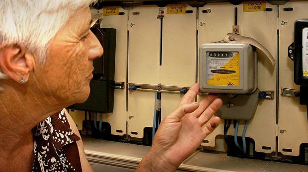 Una señora revisa el contador de la electricidad.