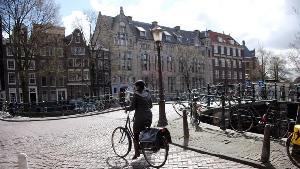 Una mujer circula en bicicleta por una calle de Amsterdam