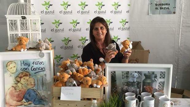 Elo Pereira Coronil en el stand de su tienda de quesos con las cabritas solidarias y otros objetos de ANDEX