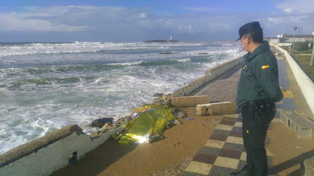 Efectivo de la Guardia Civil custodia el cuerpo del migrante fallecido ahogado.