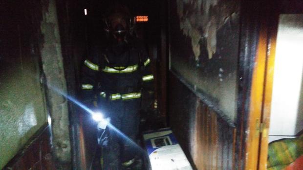 Bombero en una casa que ha sufrido un incendio (imagen de archivo)