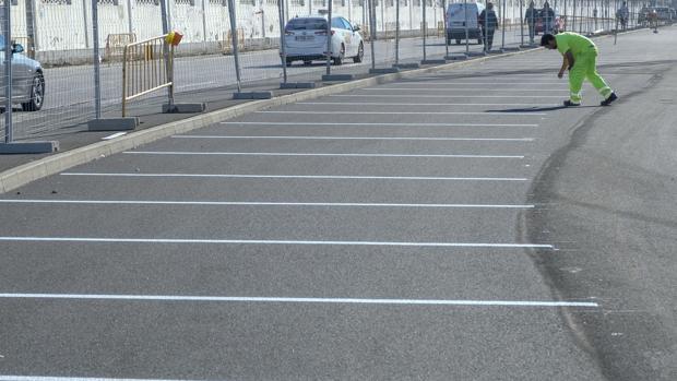 Operarios ultimando la puesta a punto del parking gratis al aire libre en la avenida de Astilleros.