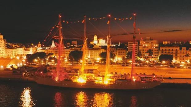 Vista aérea del Juan Sebastián de Elcano en el puerto de Cádiz iluminado con la bandera de España.
