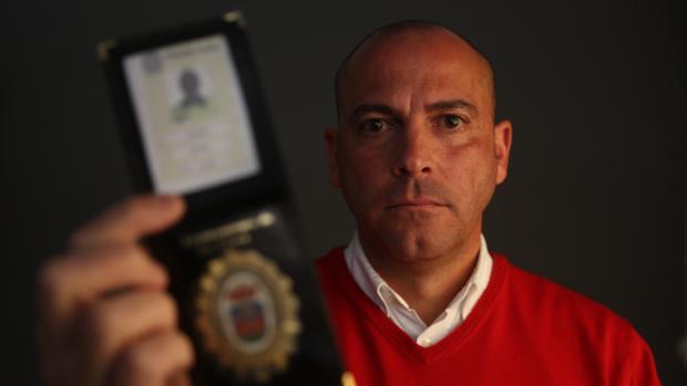 Ernesto Pérez Vera muestra su placa de policía.