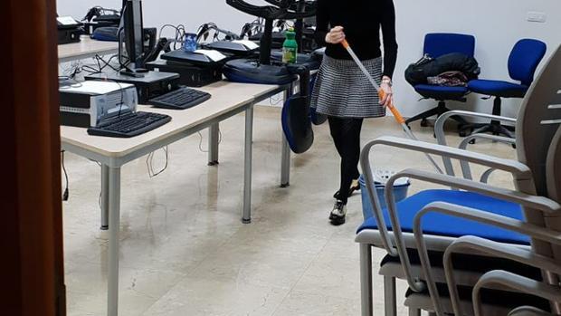Una alumna limpiando el aula con productos traídos de casa.