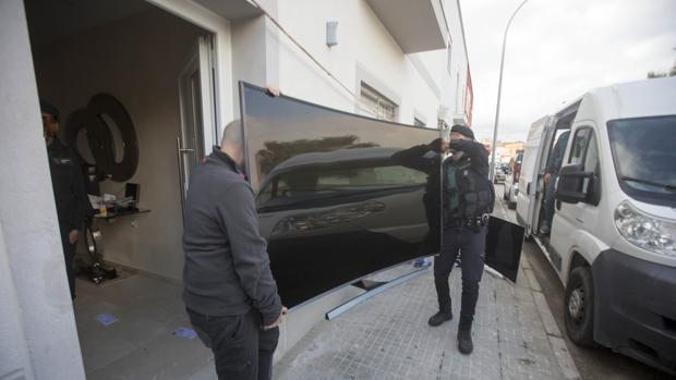 Agentes de la Guardia Civil cargan en el furgón una televisión incautada en la casa de Tejón.