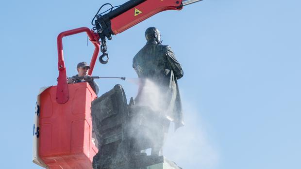 Los operarios limpian la estatua de Moret, sita en la plaza de San Juan de Dios, delante del Ayuntamiento de Cádiz.