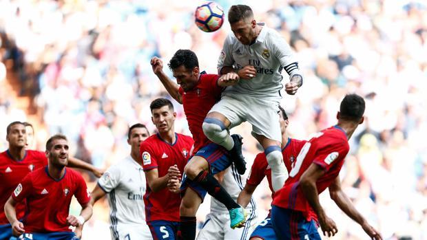 Sergio Ramos remata de cabeza rodeado de jugadores de Osasuna