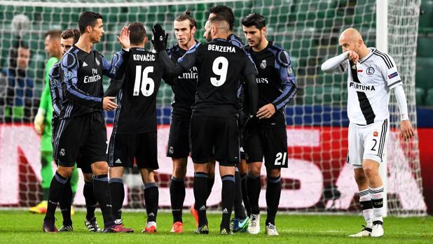 Benzema es felicitado por su gol en Varsovia