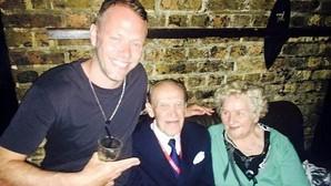 Los ancianos posan junto al dueño del bar