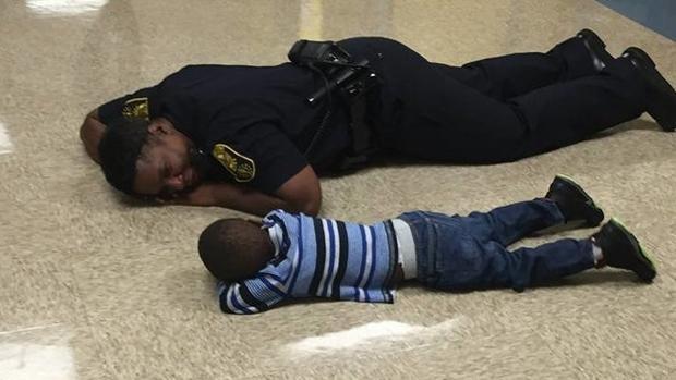 Momento en el que la policía se tumba junto al niño en el suelo del colegio