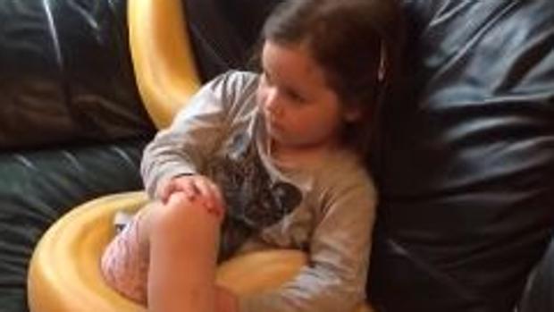 Una niña ve la televisión acompañada de una serpiente