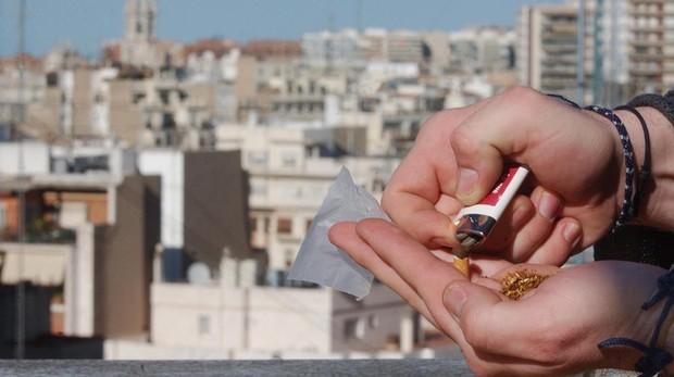Un joven lia un cigarrillo