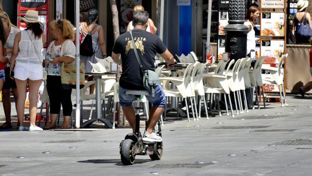 Usuario de un patinete eléctrico esta verano por el centro de Sevilla usando el carril bici