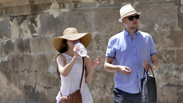 Unos turistas se refrescan mientras pasean por las calles de Sevilla